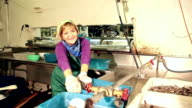 Senior woman working in seafood processing plant video