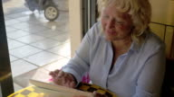 Senior woman working with tablet PC in cafe video