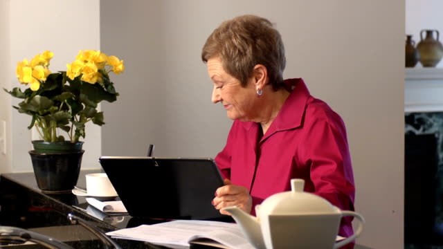 Senior Woman Works with Documents and Digital Tablet video