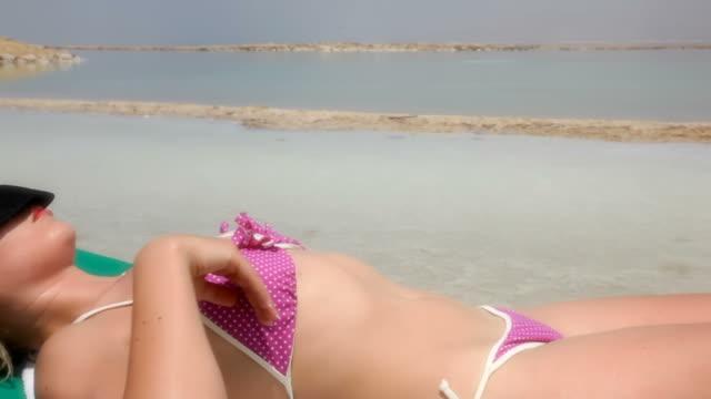 Sensual lady sunbathes on the Dead Sea video