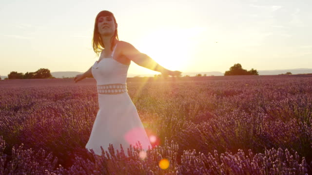 SLOW MOTION: Sensual woman in white dress enjoying in beautiful lavender field at sunset video