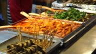 Seoul, Korea street food stall, tteokbokki, fish hotdog, soondae and other food on stick video