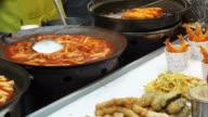 Seoul, Korea variety of Korean street food stall, tteokbokki, fish hotdog, sausage and other fried food on stick video