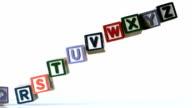 Separated alphabet blocks falling over video