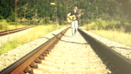 Sepia toned footage of a young man walking along the railway playing guitar video