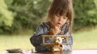 HD Sequence. GENDER NEUTRAL KIDS. Happy Child Painting a Wooden Airplane Model on a Beautiful Summer Morning at The Porch. video