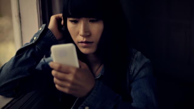 Serene Asian girl sitting near window and using phone. video