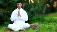 Serene young man doing meditation outdoors video