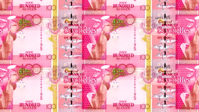 Series of banknotes of one hundred rupees of the bank of the Seychelles Island rolling on screen, coins of the world, cash money, loop video