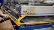 Serigraphy print bags machine in printing factory operator female hand video