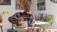 4К Serious artist painting in workshop video