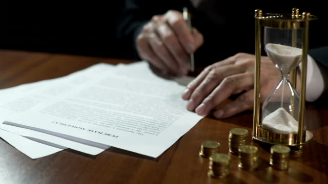 Serious businessman signing purchase agreement as time flows with sand in clock video