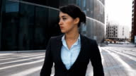 Serious businesswoman walk outdoor and look at camera video