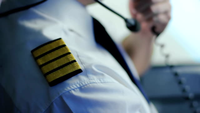 Serious captain of airliner transmitting information by radio, job duties video