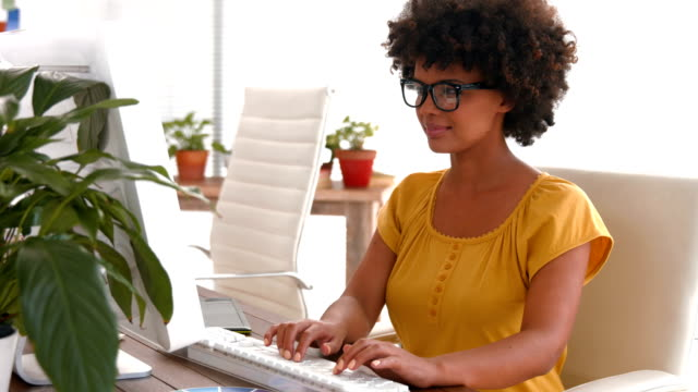 Serious casual businesswoman using computer video