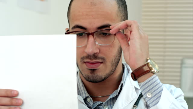 Serious doctor checking important medical analysis video