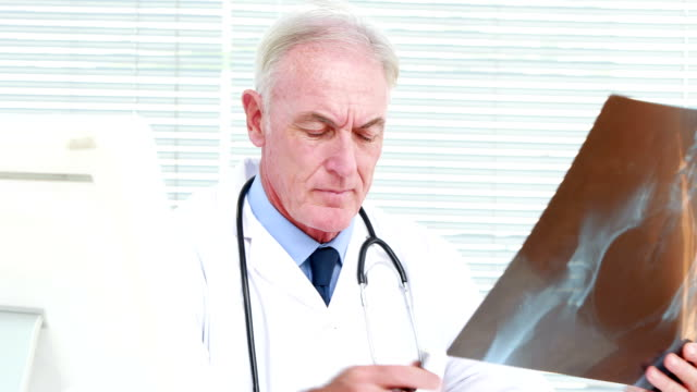 Serious doctor examining a pregnant woman x-ray video