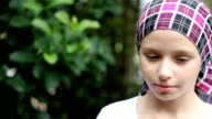 Serious expression on female cancer survivor with headscarf video