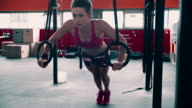 Serious girl doing exercises with gymnastic rings video