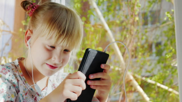 A serious girl of 6 years old listens to music, plays on a smartphone. Sits in front of the window. Spring weather and mood video