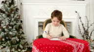 Serious little boy writing letter to Santa sitting at the table near the Christmas tree video