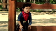 Serious little cowboy sitting on a wooden fence video