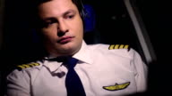 Serious male pilot in civil aviation uniform looking at flight control panel video