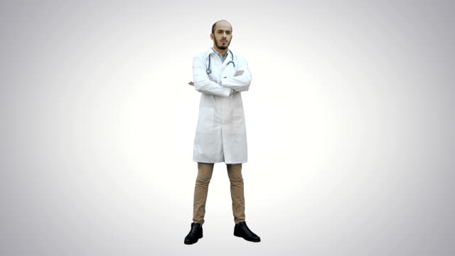 Serious medical worker standing and folding his arms on his chest on white background video