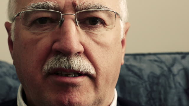 Serious older man with a mustache stares intently at the camera video