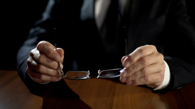 Serious politician putting glasses on table, planning election campaign strategy video