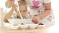 Serious pretty little girl concentrating on baking video