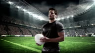 Serious rugby player holding rugby ball video