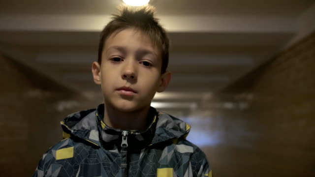 serious street boy looking at the camera in the tunnel video
