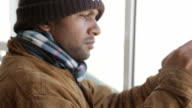 Serious warmly-dressed man-Hindu takes pictures with smart phone through a window in winter video