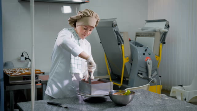 Serious woman standing behind povarsikim pastry table on the background of mechanical harvester confectionery and chocolate cake shovel cuts from metal mold and then removing it video