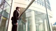 Serious young businessman standing on the balcony video
