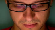 Serious young man in black rim glasses using his tablet computer. Screen reflecting in the glass. FullHD close up video video