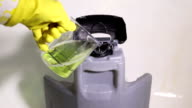 Service cleaner pours detergent into the tank of the vacuum cleaner video