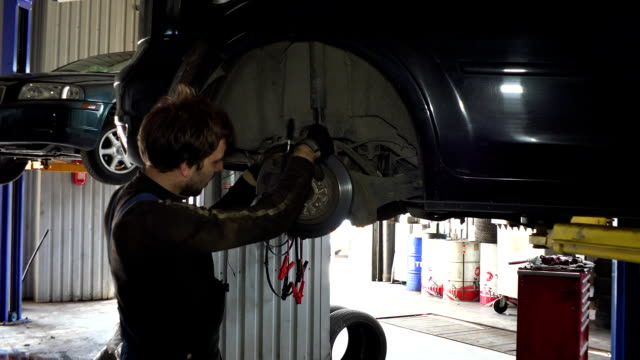 service worker man repair automobile brake system. video