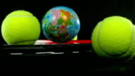 Set of tennis ball and tennis racket, a ball with the globe falling over it video