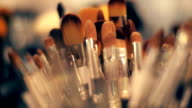 A set of various size and different color brushes for powder in the store video