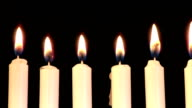 Seven lit candles in Menorah on a black background video