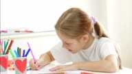 Seven years old girl drawing and coloring on a paper at home. video