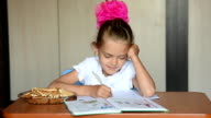 Seven-year girl schoolgirl doing homework distracted and looked into the frame video