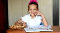 Seven-year girl schoolgirl doing homework snacking biscuits video