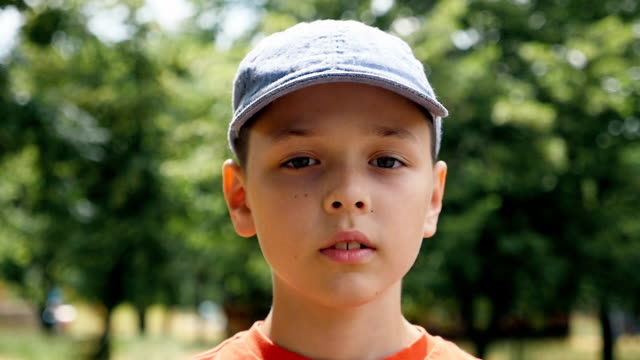 A seven-year-old boy stands in a park on a picturesque lawn and thinks in slo-mo video