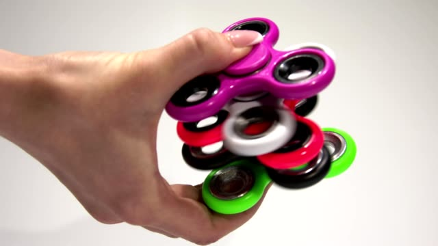 Several multi-colored spinners in hand. video