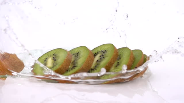 A Several Slices of Kiwi are Falling on the Table. video