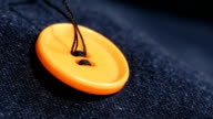 Sewing an orange button on jeans, denim, close up video