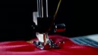 Sewing machine stitching seam on fabric. Yellow thread pattern on red fabric video